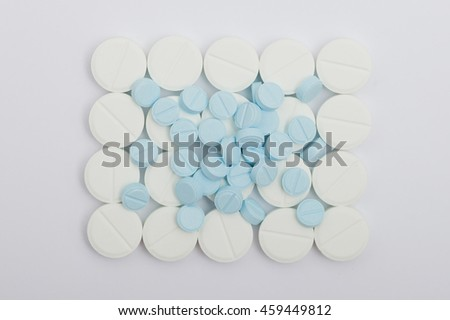 Heap of white round pills medical on a white background
