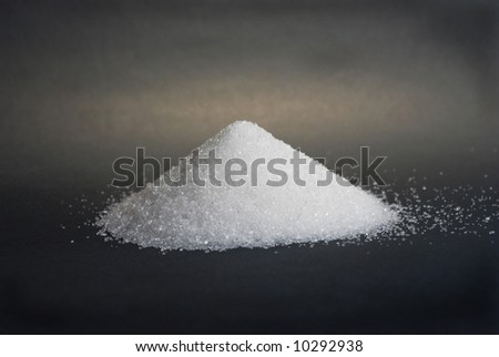 Heap of white sugar on a black background