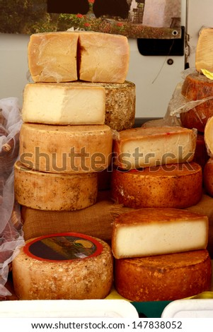 Heaps of various delicious fresh cheese wheels at an Italian market stand. - stock photo