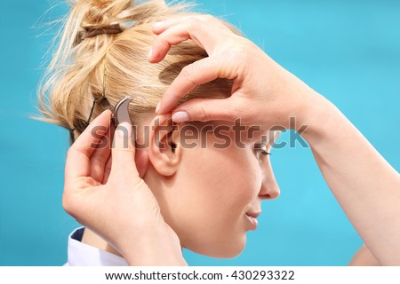 Hearing loss. The doctor assumes the woman hearing aid in your ear  - stock photo