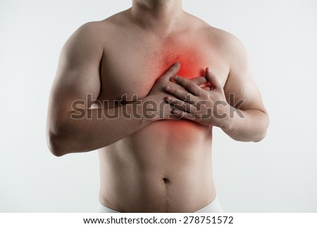 Heart ache and attack. Closeup of male torso with red point on his painful chest. - stock photo