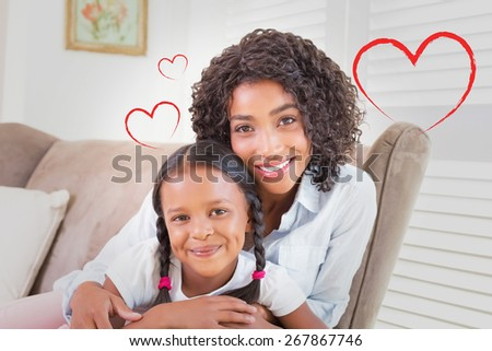 Heart against pretty mother sitting on the couch with her daughter smiling at camera - stock photo