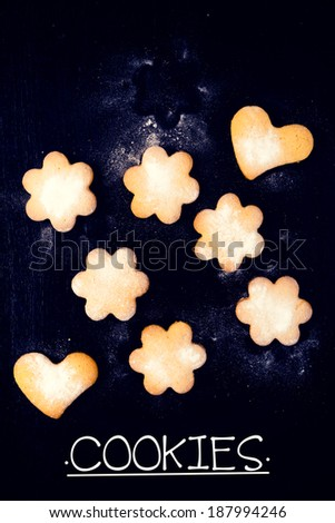 Heart and star shape cookies on the black wooden background from above - stock photo