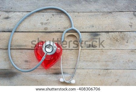 Heart and stethoscope , health care concept on wooden background - stock photo