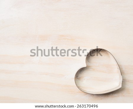 Heart biscuit cutter bake tool on white wooden background, top view,place for text - stock photo