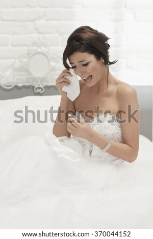Heart-broken bride holding engagement ring, crying on wedding-day, looking unhappy.