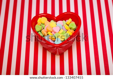 Heart Candy Dish Striped a heart shaped candy dish filled with candies is on a red and white striped background.
