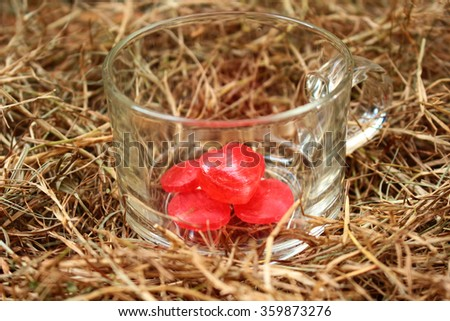 Heart candy in a glass on dried grass background.