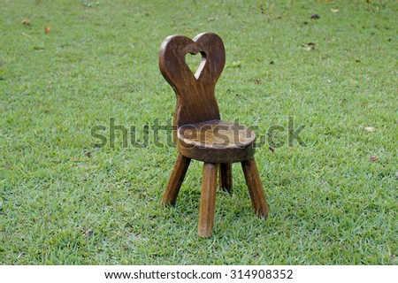 Heart carve miniature wooden chair in a green field in a Autumn afternoon - stock photo