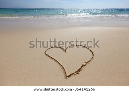 Heart drawing in the sand on the beach, blue waves on background