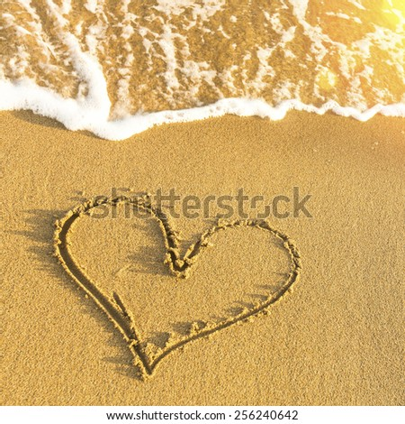 Heart drawn in beach sand, soft wave and solar glare. - stock photo