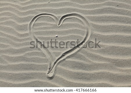 Heart drawn in the sand. Beach background. - stock photo