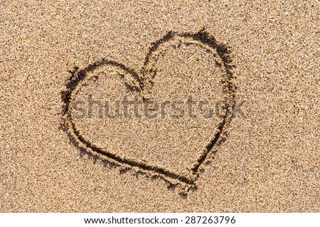 Heart Drawn On Ocean Beach Sand - stock photo