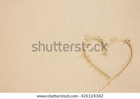 heart drawn on the beach sand texture background