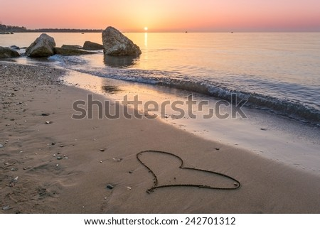 Heart drawn on the beach sand with sun above the horizon - stock photo