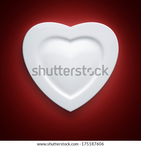 Heart form white plate on red background  - stock photo