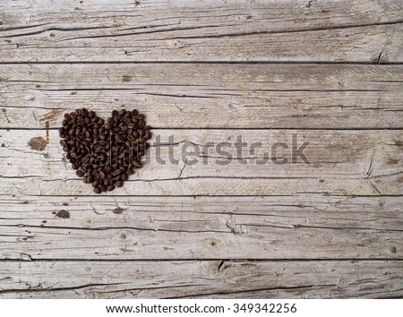 Heart from coffee beans on wooden background - stock photo