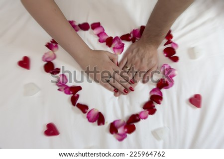 Heart from petals and wedding rings - stock photo