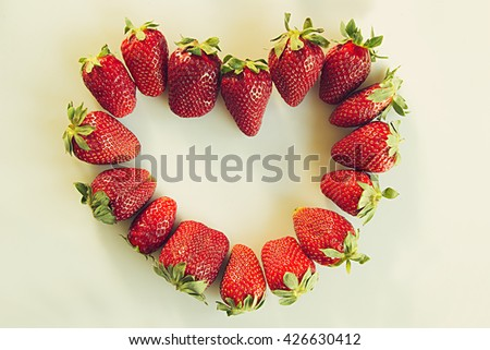 Heart from ripe strawberry whole. View from above. Heart background. Strawberry background. Fruit background. Texture. Macro. Instagram filter. - stock photo