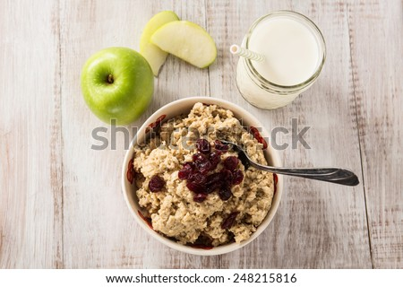 Heart healthy oatmeal breakfast cereal with apples and cranberries and glass of milk - stock photo