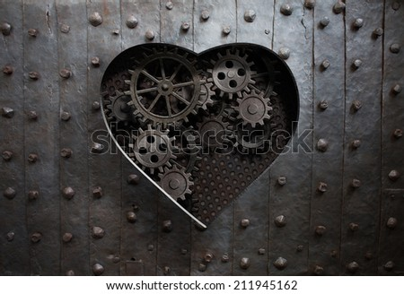 heart hole in old metal with gears and cogs - stock photo