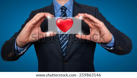 Heart in front of businessman. Blue background - Stock Image - stock photo