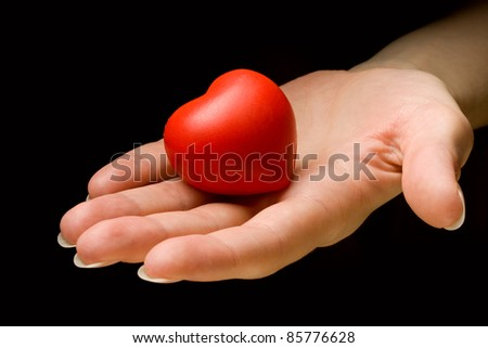 Heart in hand isolated on black background