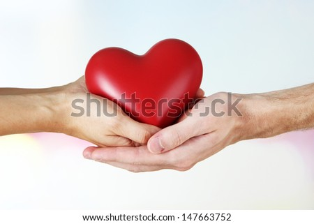 Heart in hands on light background