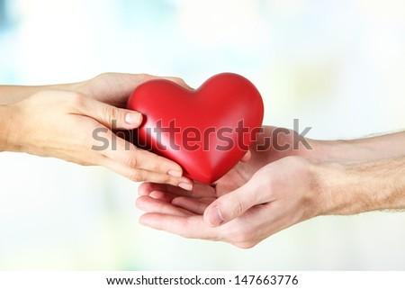 Heart in hands on light background - stock photo