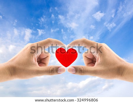 heart in hands on sky background, concept healthcare and valentine's day