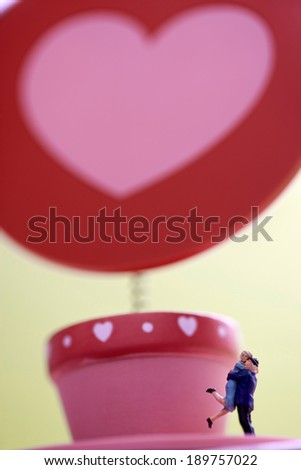 Heart in pink pot with hugging dolls - stock photo