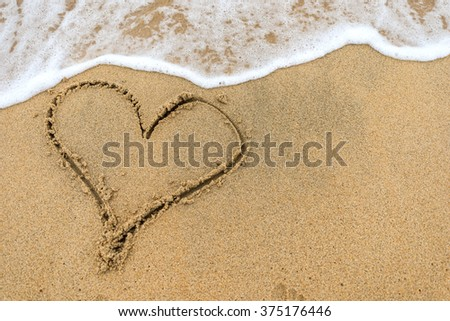 Heart in the sand on the beach , Heart drawn on the sand of the beach with sea foam and wave