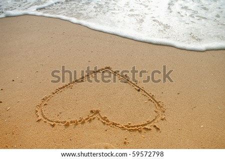 Heart in the sand with wave rolling - stock photo