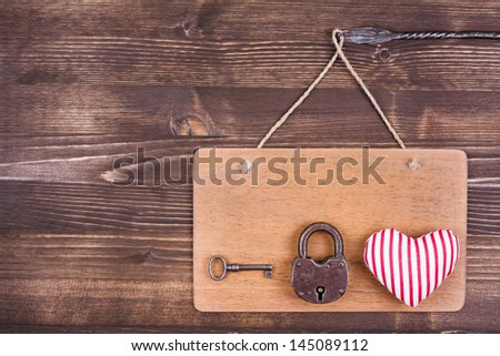 Heart, key and lock on signboard hanging on vintage wood background - stock photo