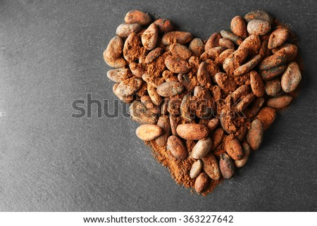 Heart made of aromatic cocoa beans on grey background - stock photo