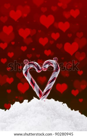 Heart made of candy cane with snow and hearts - stock photo