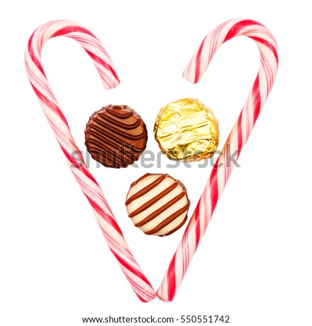 Heart made of candy canes with three chocolate candies inside isolated on white background