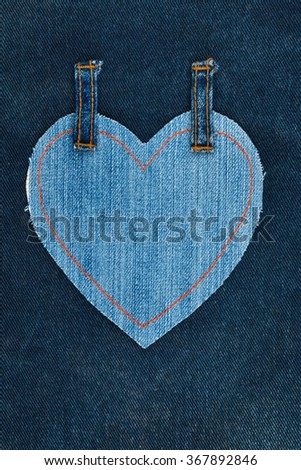 Heart made of denim fabric with yellow stitching on dark denim, with space for your text - stock photo