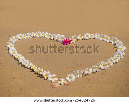 Heart made of flowers on the  beach love concept.  - stock photo