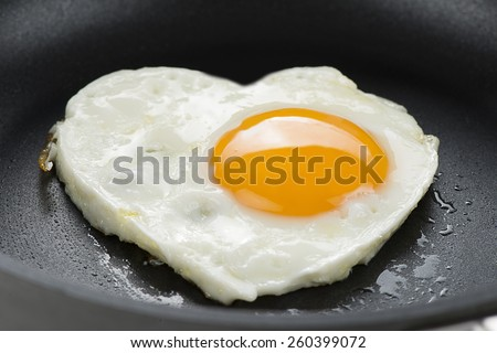 Heart made of fried egg on teflon pan.   - stock photo