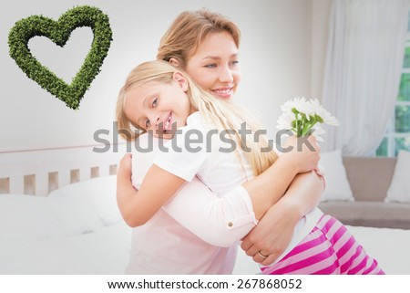 Heart made of leaves against mother and daughter hugging with flowers - stock photo