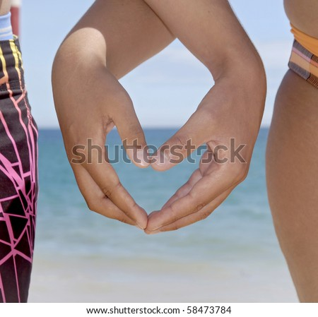 Heart made with hands in the beach - stock photo