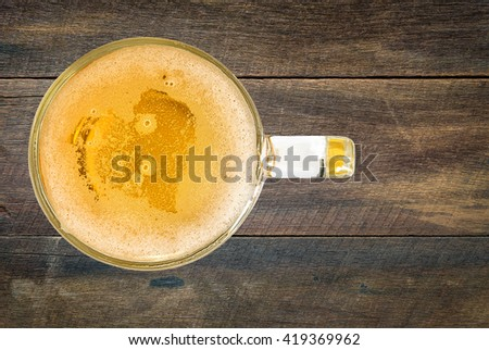 heart of beer bubbles glass of light beer on old wooden tabla in top view on a white background - stock photo