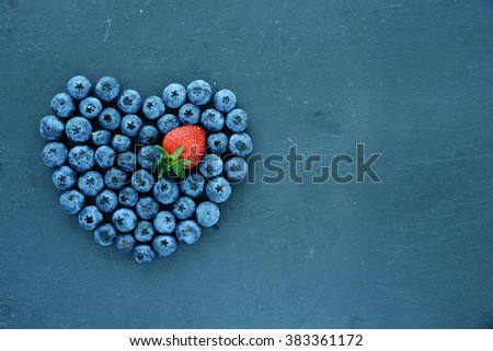Heart of berries on slate background - stock photo