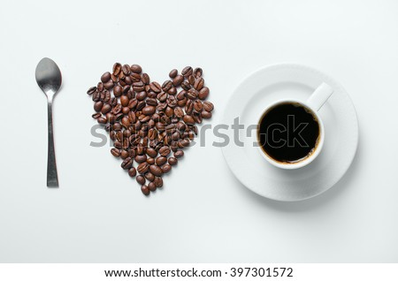 Heart of coffee beans with spoon on a white background,Coffee beans as a heart ,Coffee espresso.Coffee grains.  Heart of the coffee beans.Coffee black. - stock photo