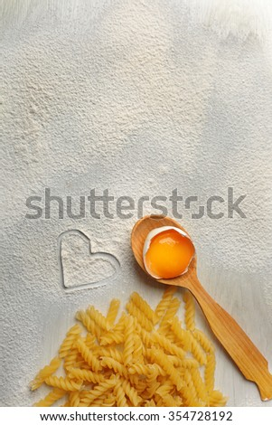 Heart of flour and pasta on gray background - stock photo