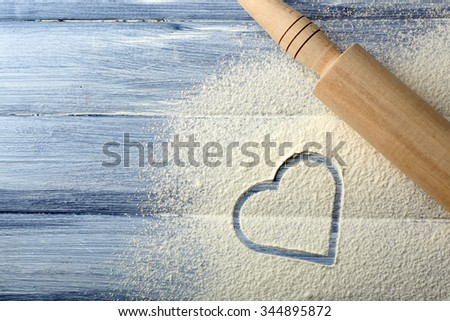 Heart of flour and rolling pin on color wooden background - stock photo