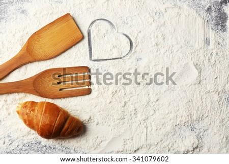 Heart of flour, croissant and  wooden kitchen utensils n on gray background - stock photo