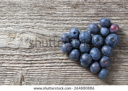 heart of fresh blueberries on a wooden background, top view, horizontal - stock photo