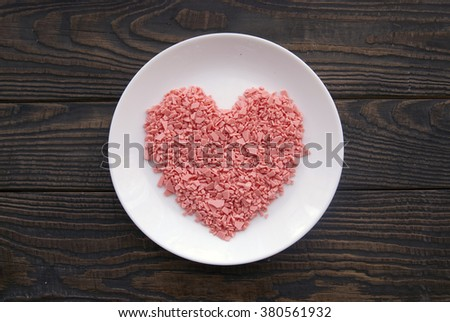 Heart of pink chocolate drops on a white plate. Heart of chocolate drops on a brown background. Pink chocolate heart - stock photo
